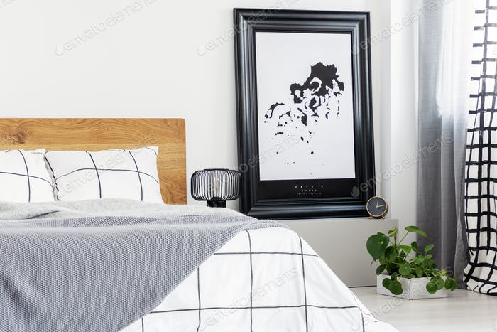 Black and white map in black frame in trendy bedroom interior with chequered bedroom