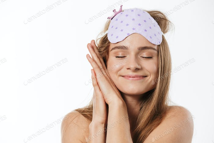 Beauty portrait of blonde half-naked woman wearing sleeping mask smiling