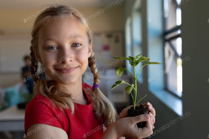Schoolgirl standing holding a seedling plant in earth in an elementary school classroom