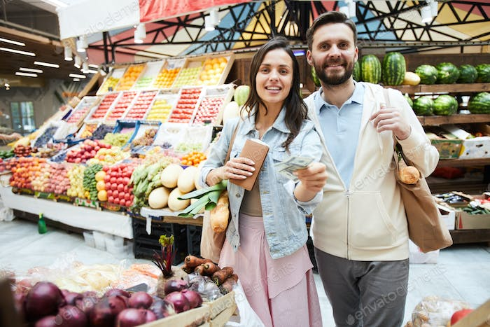 Positive beautiful couple paying for purchase at farmers market