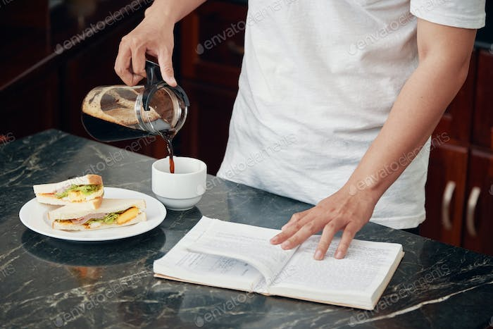 Crop man with book pouring coffee for breakfast
