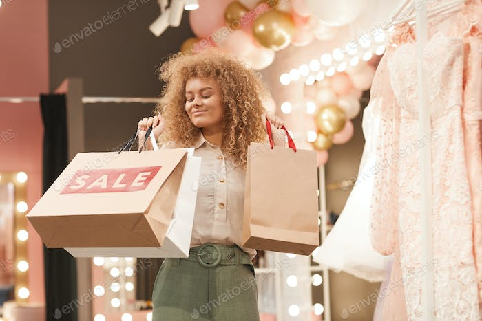 Young Woman Holding Shopping Bags in Boutique