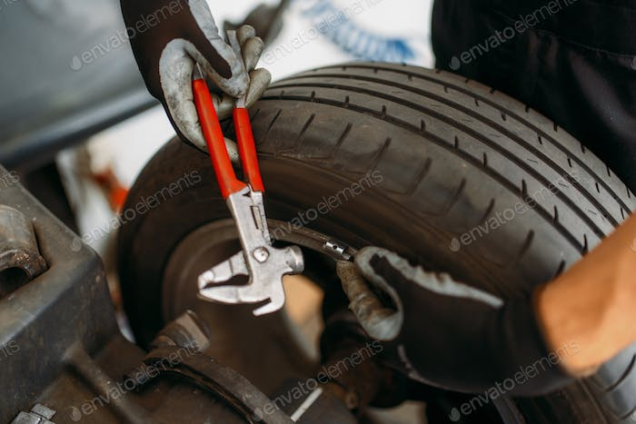 Auto mechanic balancing wheel, tire service