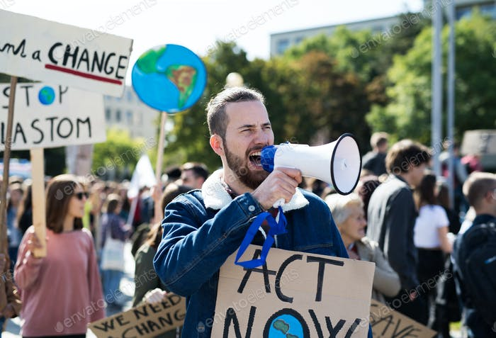 Man with placards and amplifier on global strike for climate change, shouting