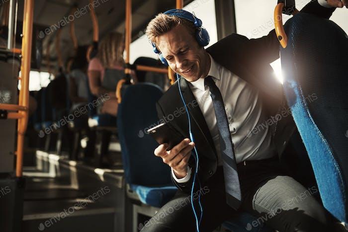 Улыбающийся бизнесмен слушает музыку во время езды на автобусе