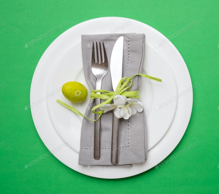 Easter egg in a white plate, gray napkin and cutlery, green color background, top view