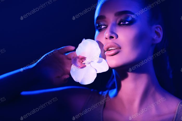 Woman with white orchid illuminated by neon lights