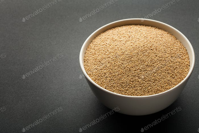 amaranth seeds in ceramic bowl isolated on dark background