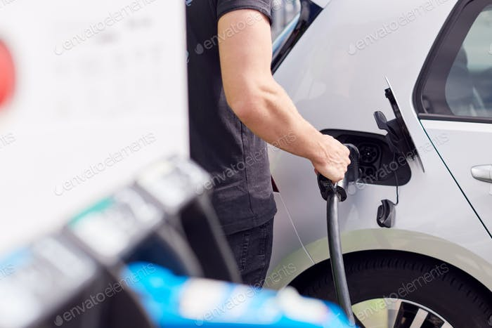 Close Up Of Man Attaching Power Cable To Environmentally Friendly Zero Emission Electric Car