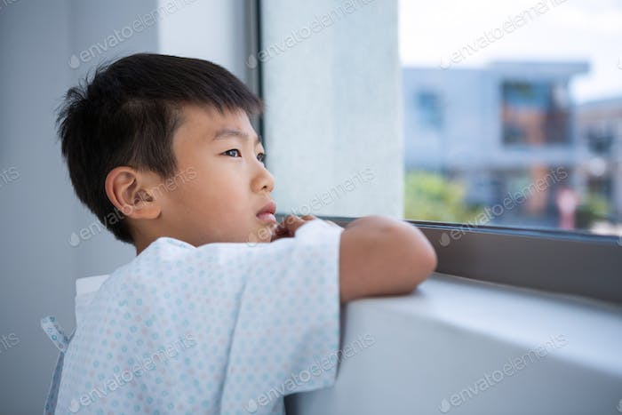 Boy patient looking out from the window at hospital