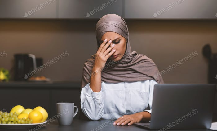 Unhappy Muslim Woman At Laptop Sitting In Kitchen At Home
