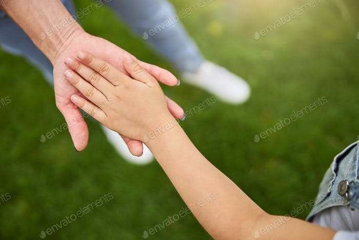 Little hand of girl on the woman hand isolated in the green grass