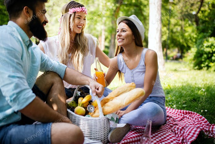 Happy friends in the park having picnic on a sunny day