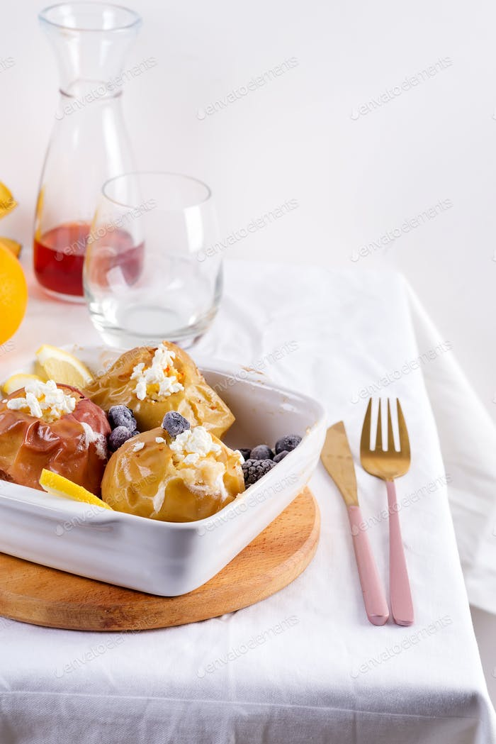 Baked apples with blueberries and cottage cheese in bowl with cutlery on white table