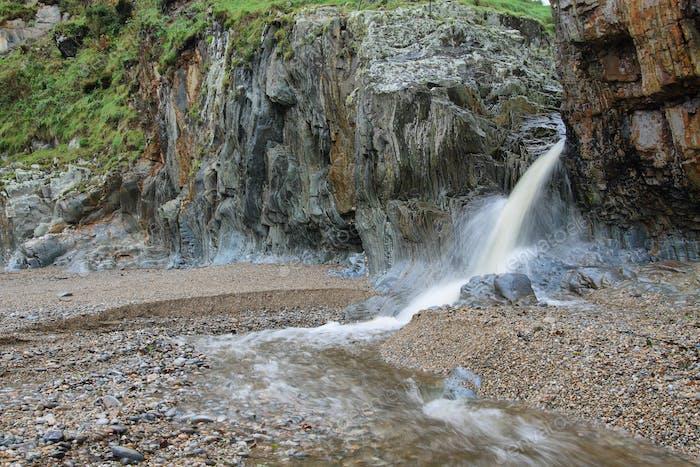 Little waterfall in beach of Silence, Asturias (Spain).