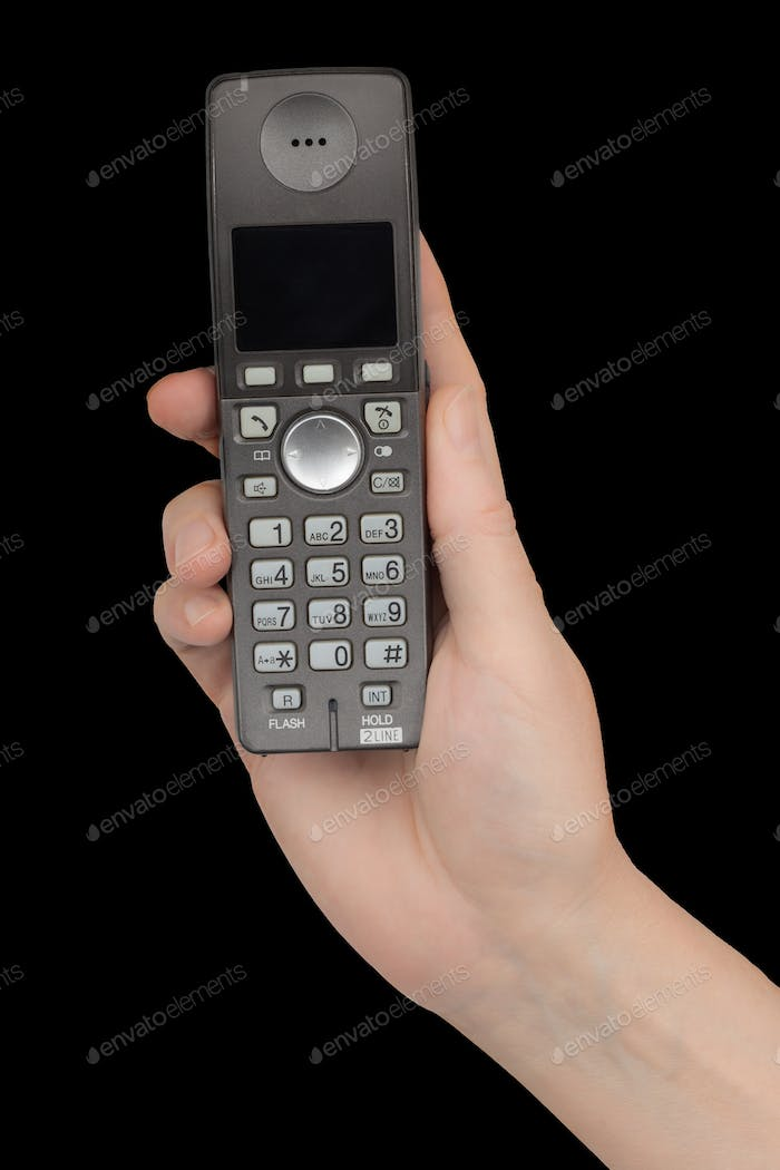 Female hand holds a phone, isolated on black background
