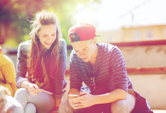 happy teenage friends with smartphones outdoors