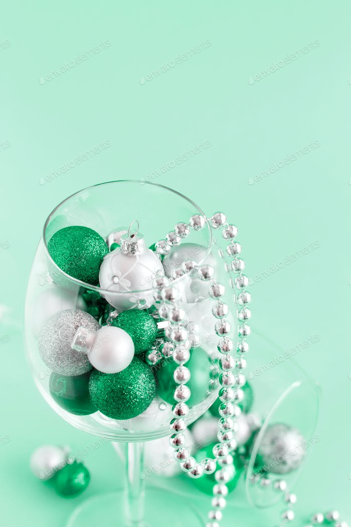 Christmas baubles in a wine glass on a light green background