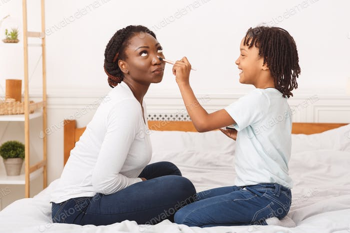 Happy african child doing makeup for mommy