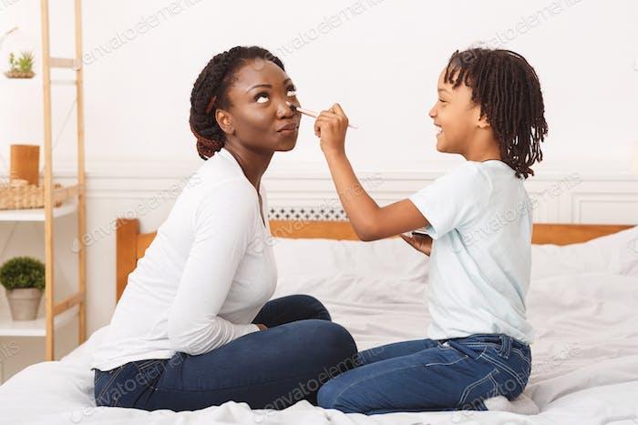 Счастливый африканский ребенок делает макияж для мамы