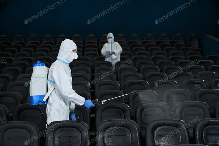 Workers cleaning cinema hall with special disinfectants