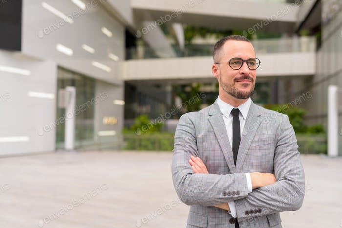 Handsome Hispanic bald bearded businessman thinking with arms crossed in the city