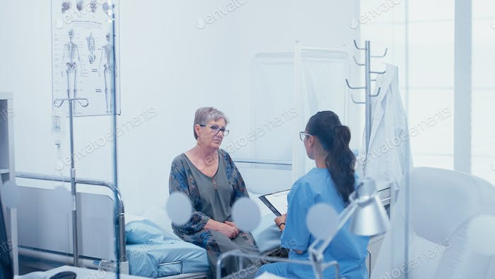 Senior patient in hospital bed talking with nurse