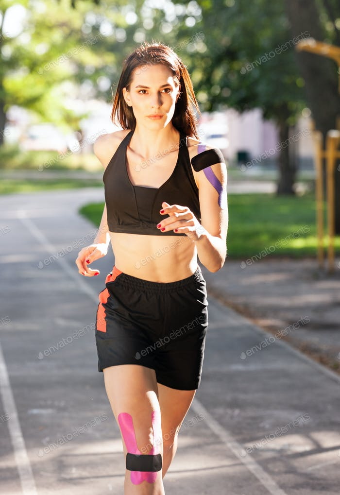 Athlete with kinesiological taping running outdoors