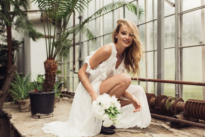 Young pretty smiling bride in white dress sitting down holding l