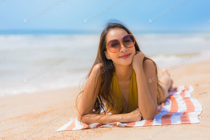 Portrait beautiful young asian woman smile happy on the beach an