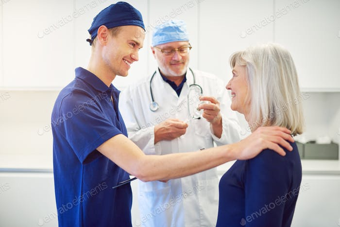 Young doctor cheering adult female patient in clinic