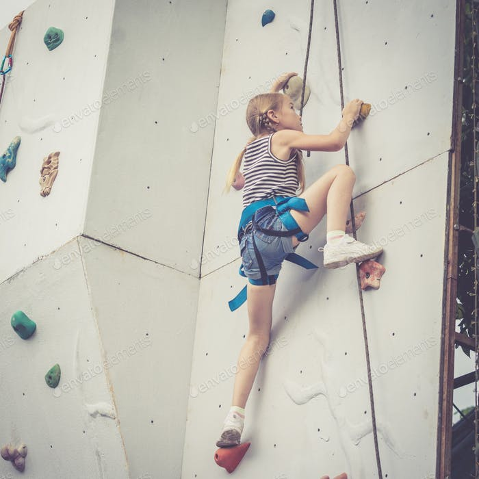 kleines Mädchen klettern eine Felswand im freien.