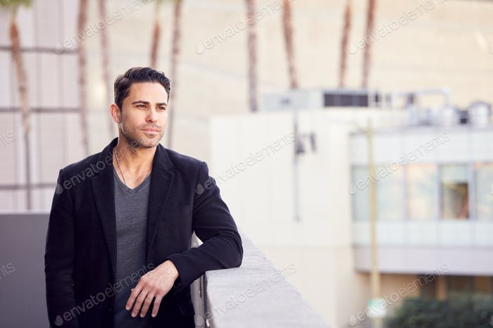 Thoughtful Businessman Standing Outside Office Building With City Skyline In Background
