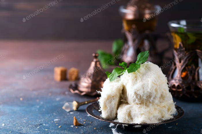 Traditional Turkish cotton candy Pismaniye in vintage plate with tea on stone background