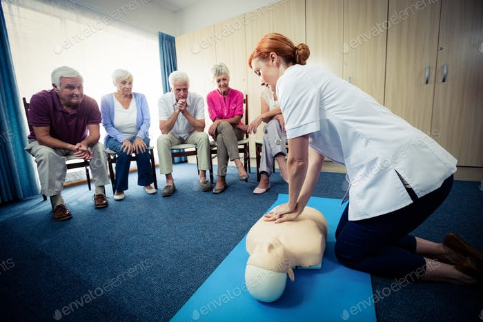 Nurse teaching first aid to a group of seniors