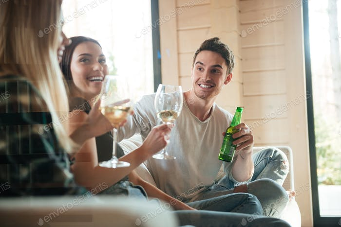 Cheerful young friends drinking wine and beer on sofa