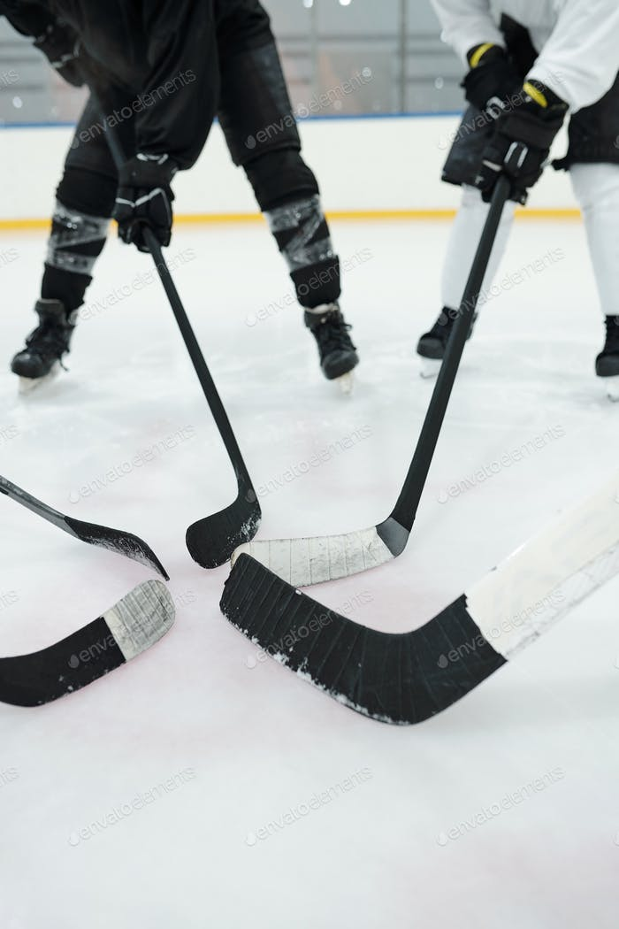 Several professional hockey players holding their sticks in front of themselves