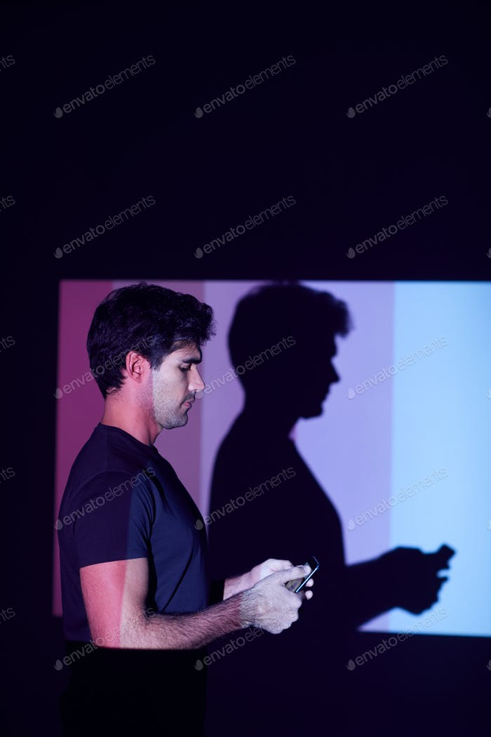 Studio Shot Of Man Using Mobile Phone With Light Casting Shadow In Background