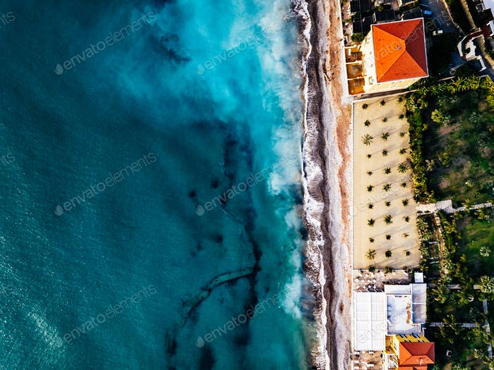 Aerial view of beach and waves. Turquoise sea water and palms, summer landscape from above.