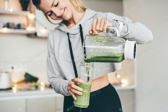 Young Woman Making Detox Smoothie At Home.