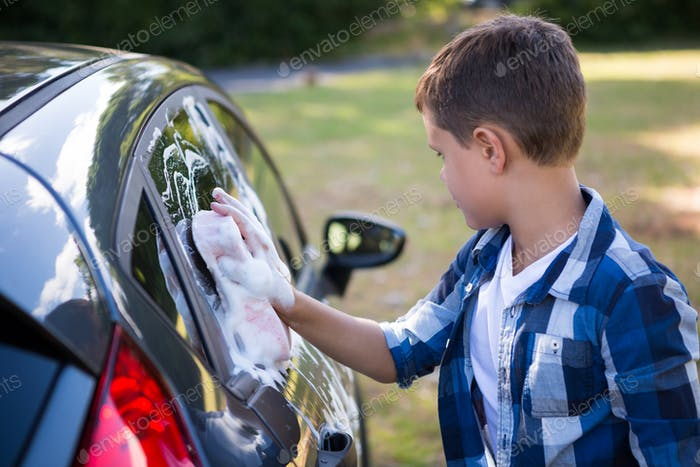 Teenage boy washing a car