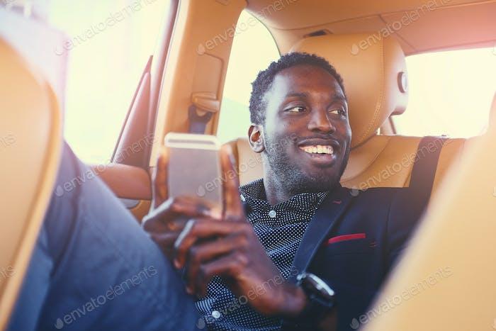 Черный мужчина с помощью смартфона в машине.