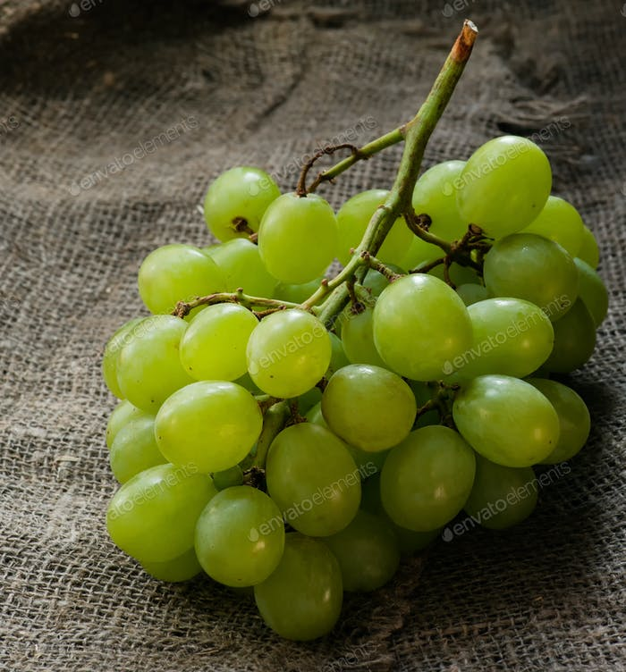 Fresh green grapes over rustic background