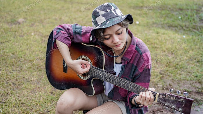 young Asian female playing guitar at camping