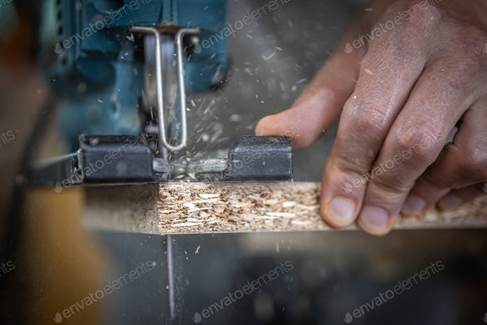Close-up process of cutting wood board with jigsaw.