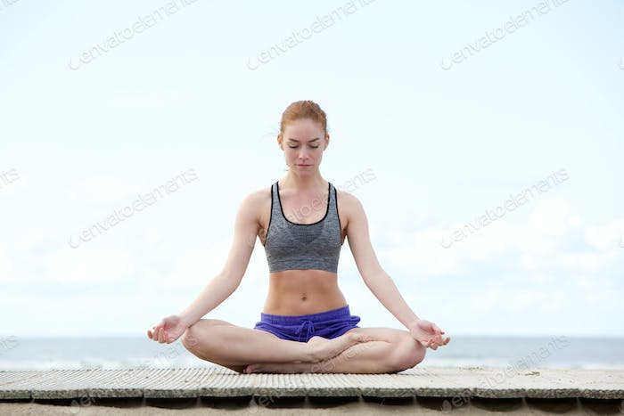 Young woman sitting outdoors in yoga position