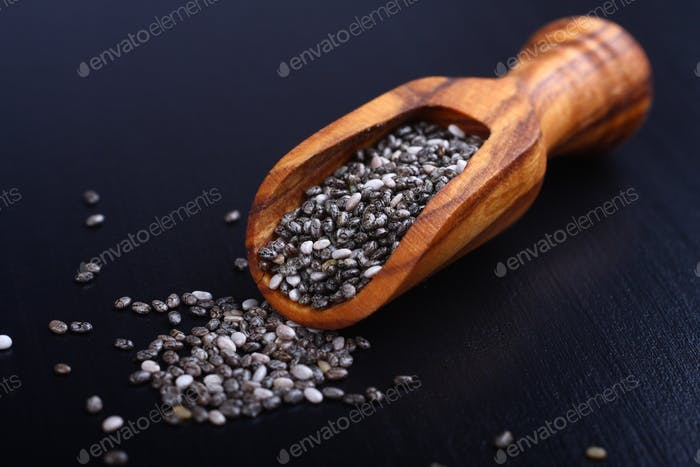 Chia seeds in wooden scoops, one of the superfoods