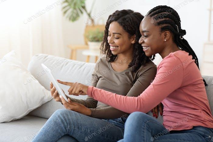 Афро-американские подруги, используя цифровой планшет вместе
