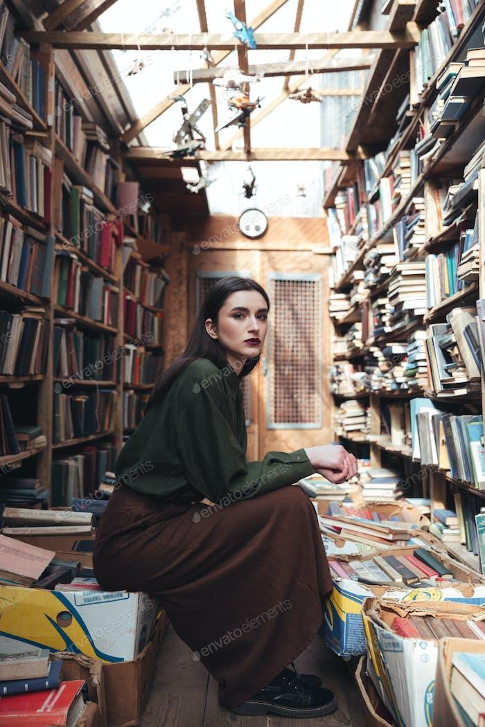 Calm woman sitting on books