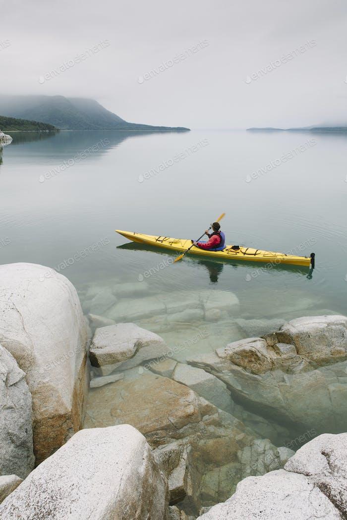 Female sea kayaker paddling in Muir Inlet, Glacier Bay National Park, Alaska